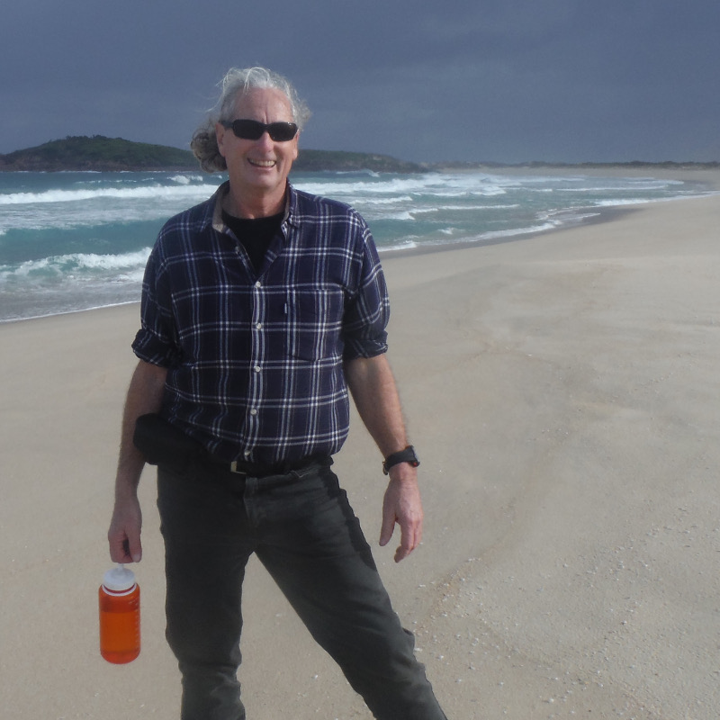 the bus driver and guide is standing on the beach during the Newcastle Small Bus Sightseeing tour