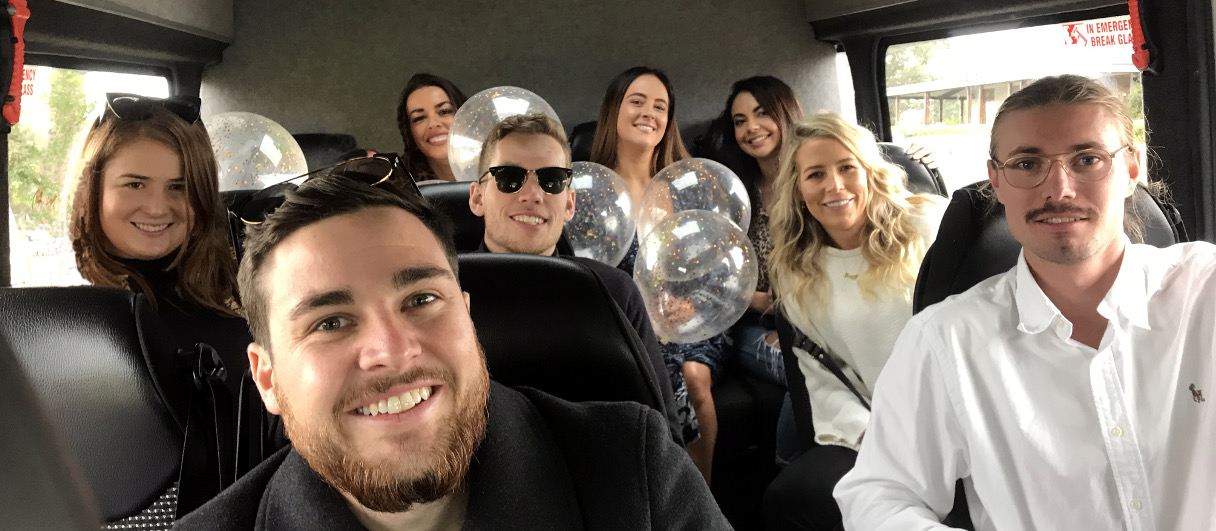 A group of people are on the shepherd mini bus with balloons going on a wine tour